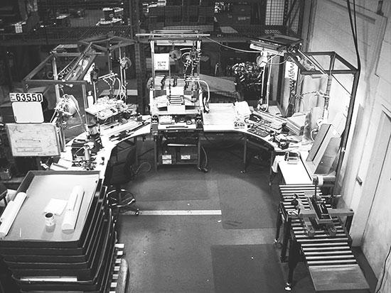 Cette image représente un exemple de cellule de travail contenant un convoyeur en « U » avec un flux de matériel partant d'une extrémité de ce « U » vers l'autre.