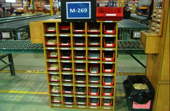 Cette image représente une étagère comportant des dépôts de stockage kanban à l'intérieur de ses cases.